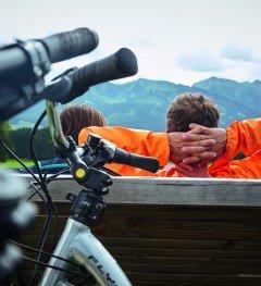 Radfahrer machen an der Radrunde Allgäu Pause und blicken auf die Allgäuer Alpen. © Allgäu GmbH